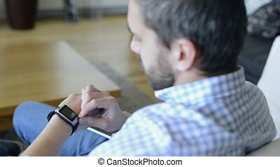 Man sitting on sofa using smartphone and smart watch