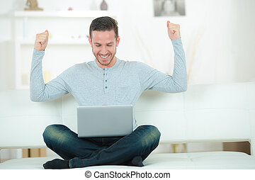 man sitting on sofa with arms up posture