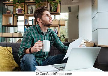 Man sitting on sofa with tea