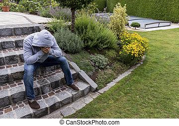 man sitting on steps - a man sitting alone on stage