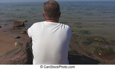 Man sitting on stone the sea