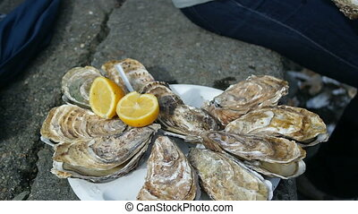 Man sitting on the bank opens an oyster and waters it with lemon juice