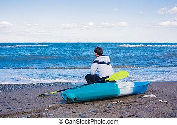 Man sitting on the beach with kayak