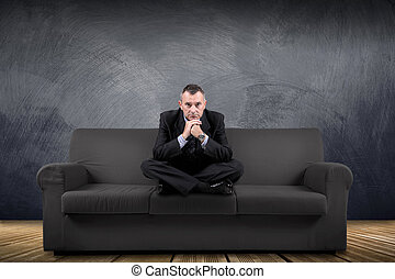 man sitting on the couch with serious look