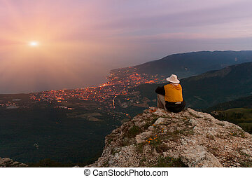 Man sitting on the edge of a cliff above the sea and looks at the sunset