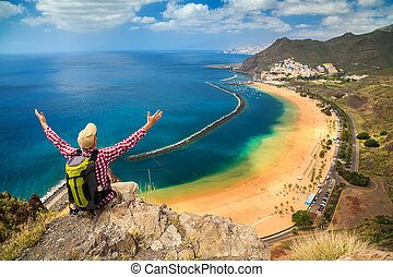 man sitting on the edge of a cliff, enjoying view of Playa de Las Teresitas