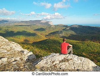 Man sitting on the edge of cliff mountain.