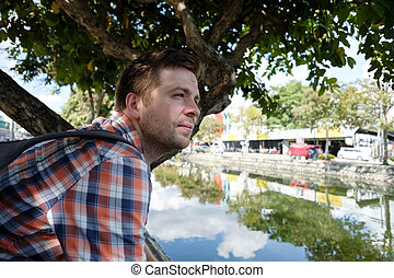 Man sitting on the embankment of a river in the city