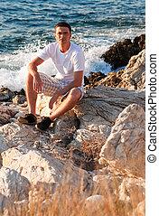 Man Sitting On The Rocks