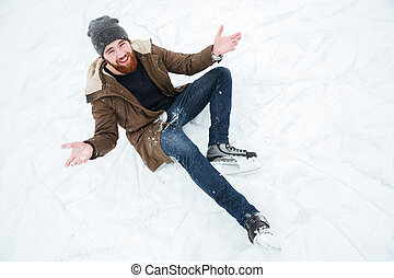 Man sitting on the snow in ice skates