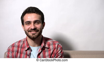 Man sitting on the sofa smiling at camera