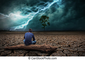 Man sitting on timber on land to the ground dry cracked and big tree. With lightning storm