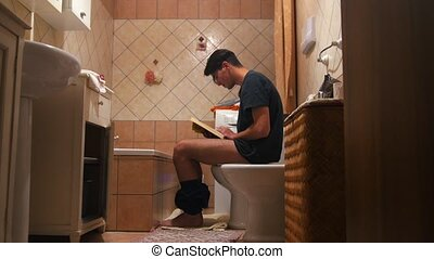 Man Sitting On Toilet and reading a book. Mid shot