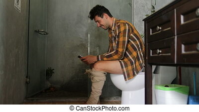 Man Sitting On Toilet Use Cell Smart Phone Young Guy...