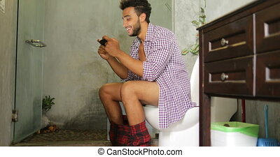 Man Sitting On Toilet Use Cell Smart Phone Young Latin Guy...