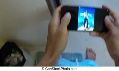 Man Sitting On Toilet Using Cell Smart Phone POV Of Guy...