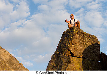 Man sitting on top of a high rock