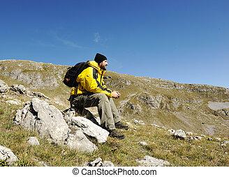 Man sitting on top of mountain