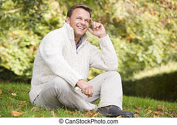 Man sitting outdoors smiling (selective focus)