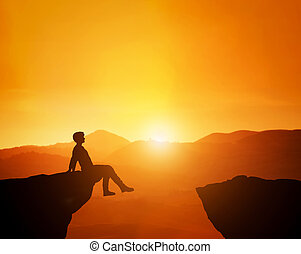 Man sitting relaxed on the edge of mountain looking at scenic sunset skyline.