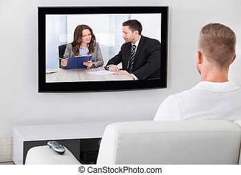 Man sitting watching television at home - Man sitting on a...