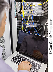 Man sitting with a laptop in front of a server