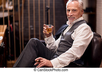 Man sitting with cognac glass and cigar