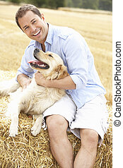 Man Sitting With Dog On Straw Bales In Harvested Field