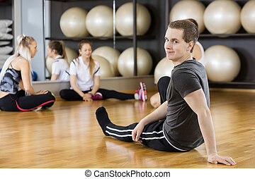 Man Sitting With Friends On Hardwood Floor In Fitness Center