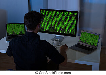Man Sitting With Laptop And Computer