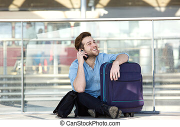 Man sitting with luggage and talking on mobile phone