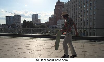 Man skater picking up skateboard after riding - Side view of...
