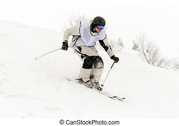 Man skiing in white clothes rapidly hurtling down the slope