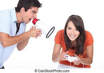 man, skrika, in, megafon, medan, kvinna, spelande video vilt