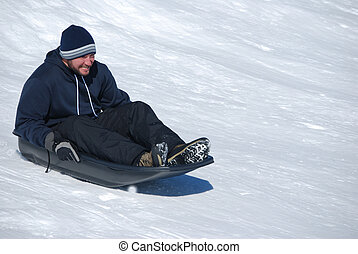 Man sledding down a snowhill