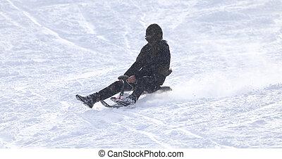 man sledding in the snow