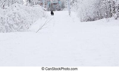On hillside sledge rides boyfriend