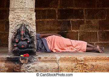 Man sleeping behing the column with Ganesha images. in Hindu...