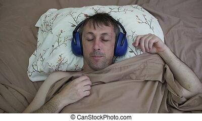 Man Sleeping Daytime With Earmuffs - Male night shift worker...
