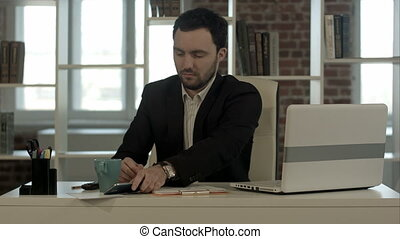 Man sleeping on a desk, wake up and start talking phone