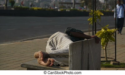 Man sleeping on a street bench