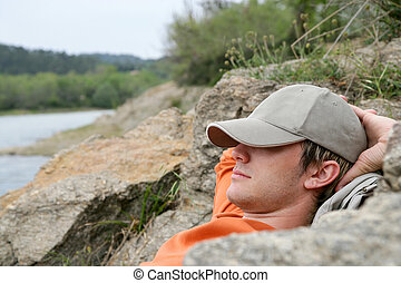 Man sleeping on the banks of a river
