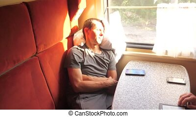 man sleeping while traveling on a train sitting in a...