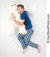 Man sleeping with large teddy bear