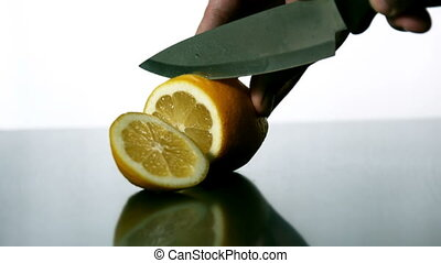 Man slicing lemon with large knife in slow motion