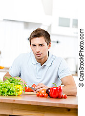 Man slicing vegetables for breakfast while sitting at the...