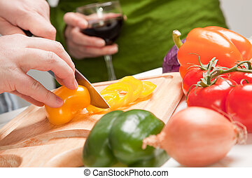 Man Slicing Vegetables on Cutting Board While Woman Enjoys a Glass of Red Wine.