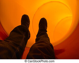 Man sliding down through a pipe slide