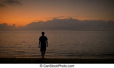 Man slowly walks into the sunrise or sunset walking into the...
