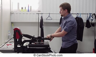 Man small business owner uses hand press to print on...